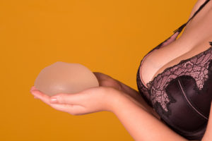 Woman in a black and pink bra holding a breast implant. Breast implant removal concept.